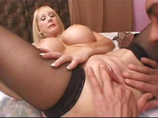 blond granny with large fake tits munches on his
