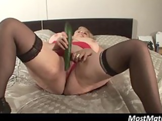blonde mature puts cucumber in her wet crack