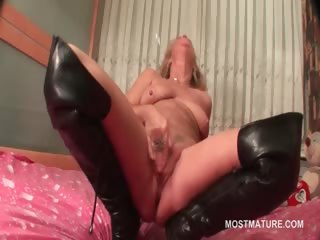 mature in leather boots doing herself in daybed